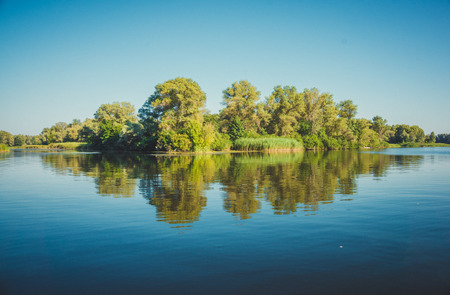 serenity: Fabulous reflection river island in serene surface of the water. Ukraine, the Dnieper river, vicinities of Kremenchuk