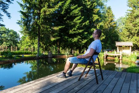 Attractive young man in glasses, t-shirt and shorts greets the dawn while sitting in front of a pond on a wooden chair Stock Photo - 126129636