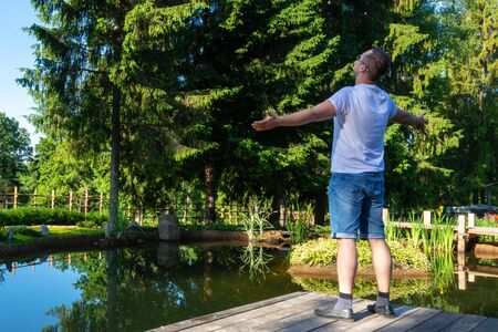 A young attractive man at dawn is standing in front of a small pond with his hands apart and looking at the sky Stock Photo - 126130057