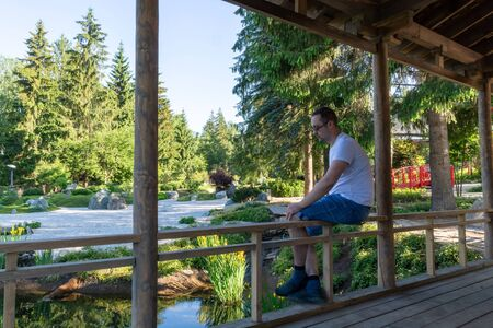 A young man sits on a wooden railing with his legs dangling down and looking at the water