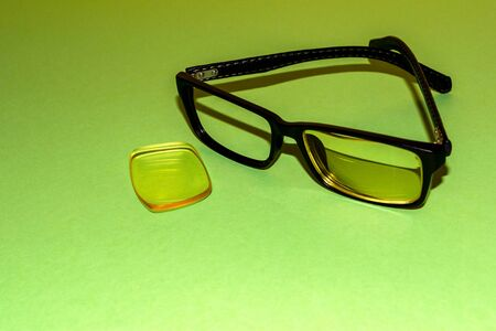Broken glasses lie on a green surface. Nearby lies a lens that has fallen out of the frame 写真素材