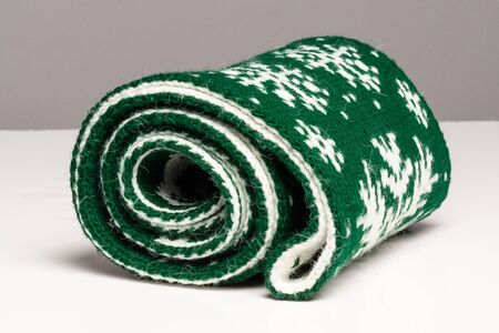 Twisted in a roll green scarf lies not a white surface on a gray background