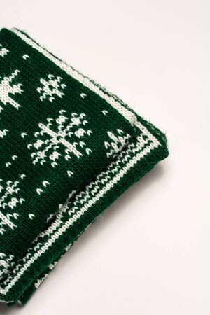Triangular fragment of green scarf with white patterns in shape of snowflakes