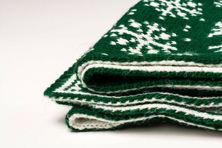Fragment folded in several layers of green scarf on white background Reklamní fotografie