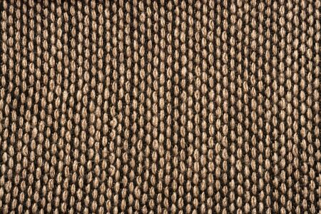 Fragment of knitted scarf of brown-black color with twisted edges. Vertical location on white background. Close-up