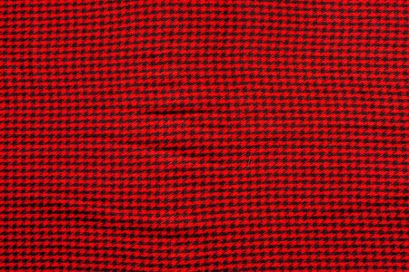 Wool cloth in a small black cage on a red background Stock Photo