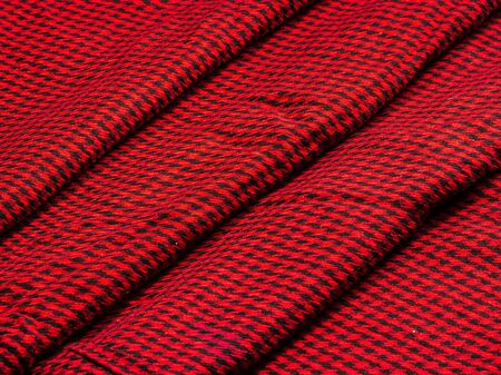 Wool cloth in a small black cage on a red background stacked with a cascade of layers Stock Photo