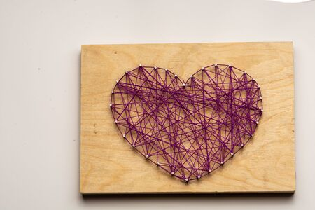 The heart is made of purple threads wrapped on nails embedded in wooden board