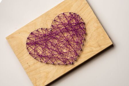 The heart is made of purple threads wrapped on nails embedded in wooden board. Diagonally. On a light background Banco de Imagens