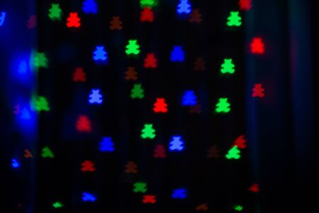 Beautiful bokeh in the form of bears of different colors on dark background