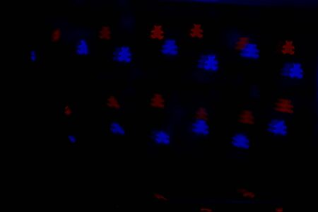 Bokeh in the form of bears of red and blue colors on dark background