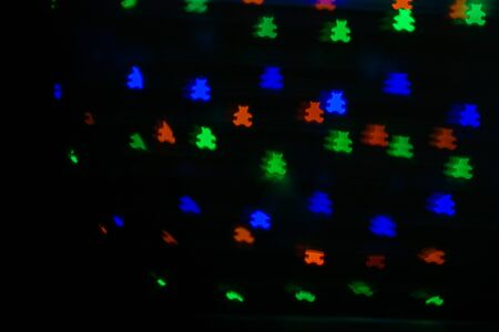 Bokeh in the form of bears of different colors on dark