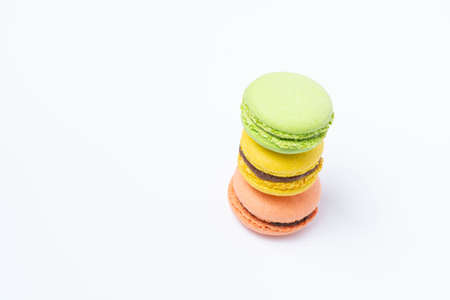 Macaroni of red, yellow and green color are stacked one on top of the other in the form of a tower on a white background
