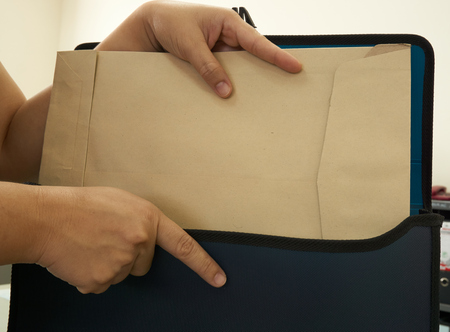 put on: Hand of woman put document in bag Stock Photo