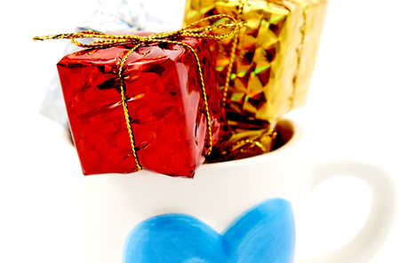 enrich: Colorful gift box in a blue heart logo cup Stock Photo