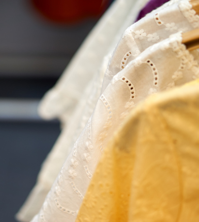 back cloth: White cloth with thai design with blurry yellow cloth in front and blurry white cloth in back