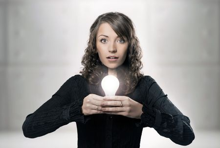 Young girl holding a light bulb photo