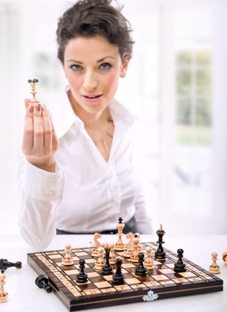 a young woman holding chess pieces