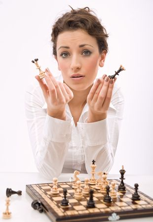 a young woman holding chess pieces, looking at camera photo