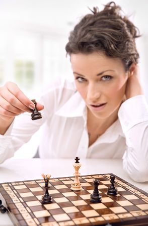 Young businesswoman playing chess photo