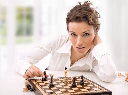 jugando ajedrez: Empresaria j�venes jugando al ajedrez Foto de archivo
