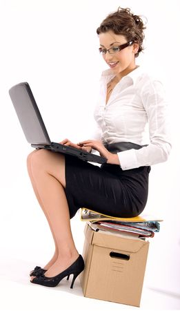 Successful young businesswoman sitting on pile of documents, lots of copy space photo
