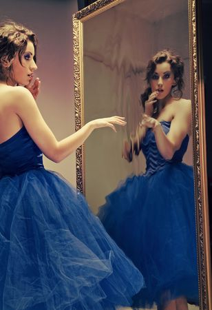 Pretty brunette looking at the mirror - vintage look photo