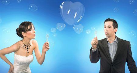 Wedding couple blowing heart shaped romantic soap bubbles photo