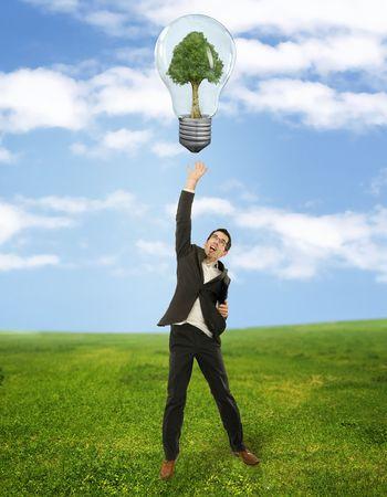 Businessman reaching green energy symbol photo