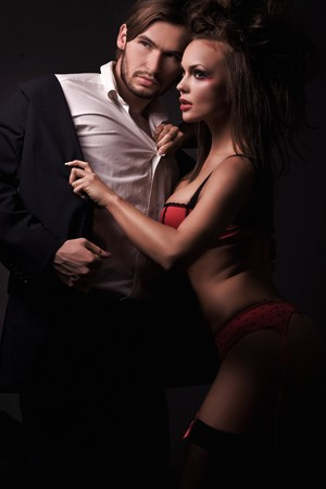 Attractive sexy couple in dark room Stock Photo - 8254898