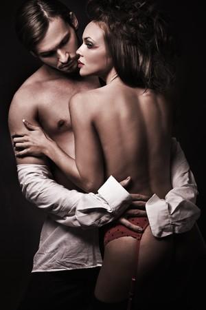 nudo maschile: sexy woman in intimo rosso, un uomo si spogliano Archivio Fotografico
