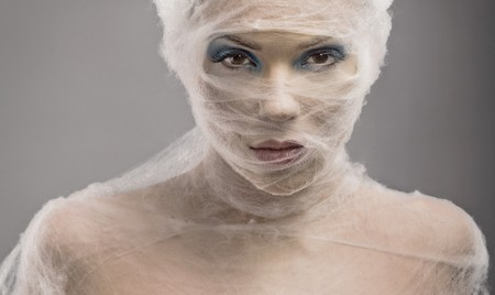 Fine art portrait of a young woman wraped with cowebs photo