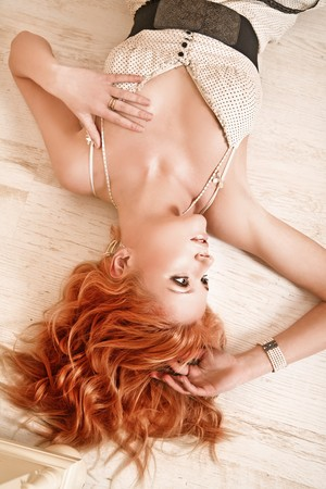 Redhead young woman lying on the floor photo