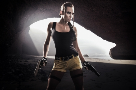Young athletic woman with gun Stock Photo