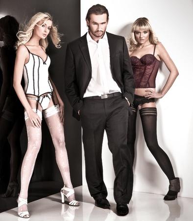 mujer con corbata: Disparo de estudio de estilo de glamour de un hombre y dos mujeres
