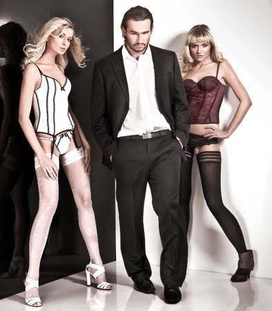 Glamour style studio shot of a man and 2 women  photo