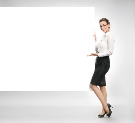Beautiful businesswoman showing empty white board  Stock Photo - 8531763