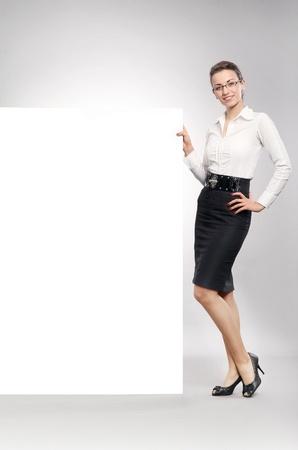 Beautiful businesswoman showing empty white board