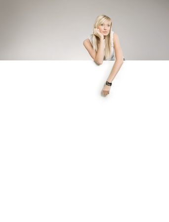 Attractive blond beauty over white board, lots of copyspace  Stock Photo - 8531749