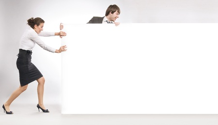 Business people pulling big white board, lots of copyspace