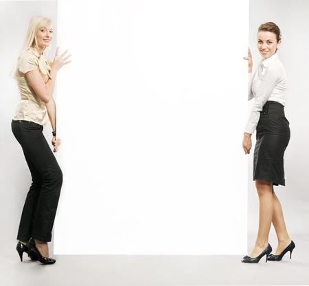 Two businesswomen carrying a big white board, lots of copyspace  photo