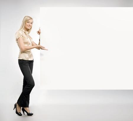 leeg bord: Mooie blonde secretaresse met een leeg bord, veel copyspace