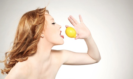 Young attractive woman holding a lemon  photo