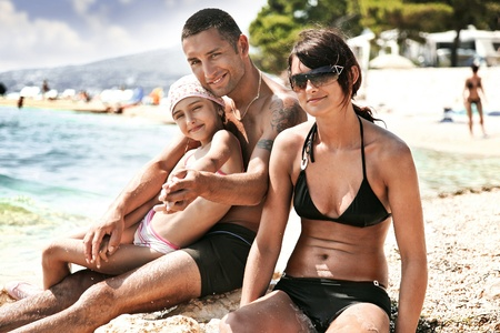 Young family embracing on a sandy beach  photo