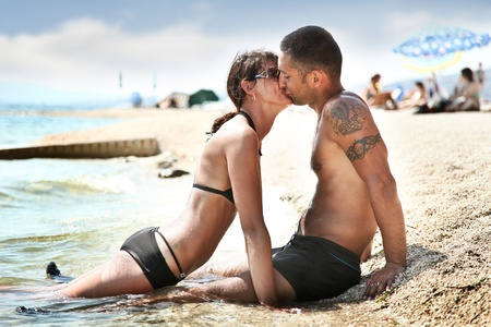 Happy couple kissing on seashore  photo