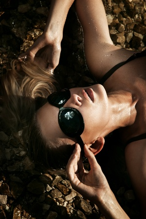 sun bathing: Beautiful young sexy blonde wearing sunglasses, laying in water
