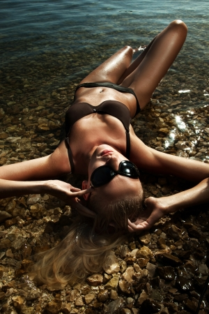 sun tan: Beautiful young sexy blonde wearing sunglasses, laying in water