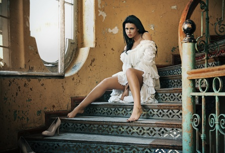 Brunette posing in on vintage stairs  photo