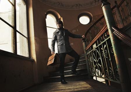 joyless: Handsome man holding a briefcase in a vintage interior
