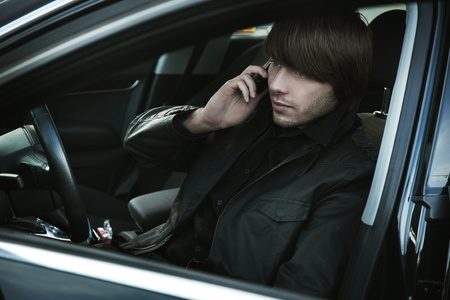 speedster: Elegant man talking over cellphone in his car Stock Photo